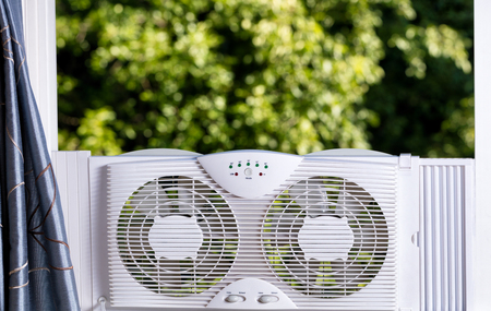 way out: Two way window fan in home window with blurred out trees in background. Stock Photo