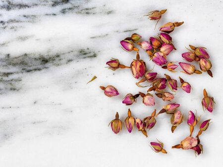 aroma: Overhead view of dry flowers on white marble stone.