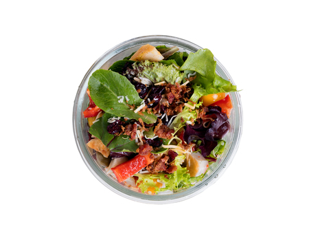 Overhead view of fresh mixed salad in glass container isolated on white background