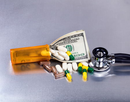 Medical cost concept with pills, bottle, stethoscope, and paper currency on stainless steel table.