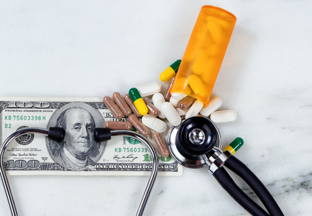 paper currency: Medical costs concept with pills, bottle, stethoscope, and paper currency.