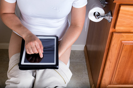 Partial view of a women using wireless internet device while sitting on the toilet. Selective focus on her index finger.