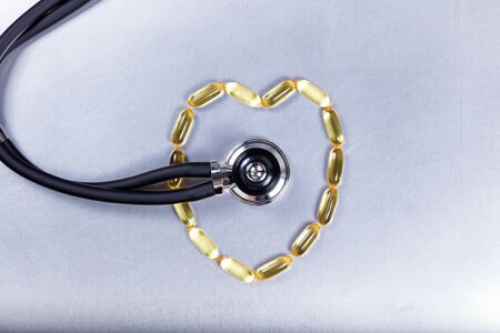 doctor fish wellness fish: Healthy heart concept with fish oil capsules and stethoscope on stainless steel. Stock Photo