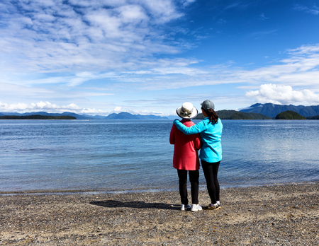 facing away: Daughter and mother, facing away from camera, enjoying the outdoors on a beautiful lake with mountains and sky in background.