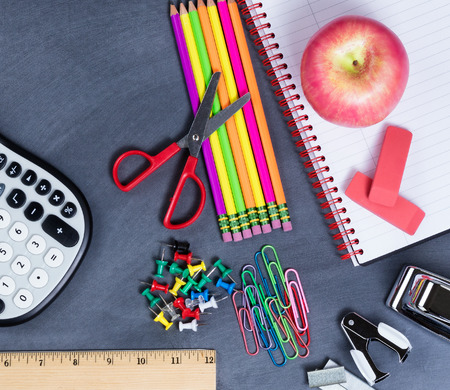 erased: Top view of back to school supplies positioned on erased chalkboard. Stock Photo