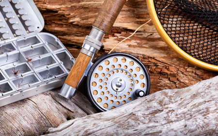 Close up view of antique fly rod, reel, landing net and lure container in stone and drift wood setting.