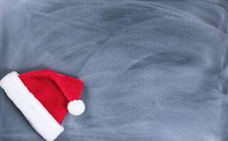 Santa cap on erased chalkboard for Christmas wish list concept.