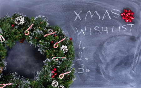 wish  list: Wreath, gift bow and candy canes on erased chalkboard with Christmas wish list written on board. Stock Photo