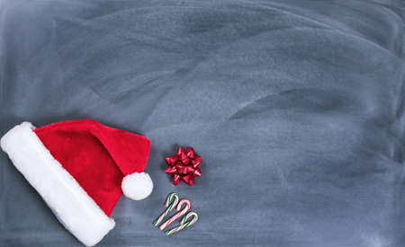 wish  list: Santa cap, gift bow and candy canes on erased chalkboard for Christmas wish list concept.