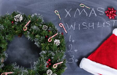 erased: Holiday Wreath, Santa cap, gift bow and candy canes on erased chalkboard with Christmas wish list written on board.