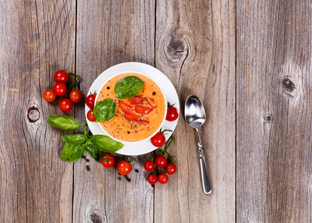 Overhead view of fresh creamy tomato soup, in white bowl, with cherry tomatoes and basil on rustic wooden boards.