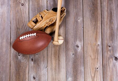 Overhead view of baseball and football equipment on rustic wooden boards. Stock Photo