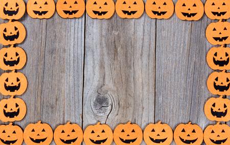 Halloween pumpkins forming complete border on rustic wood.
