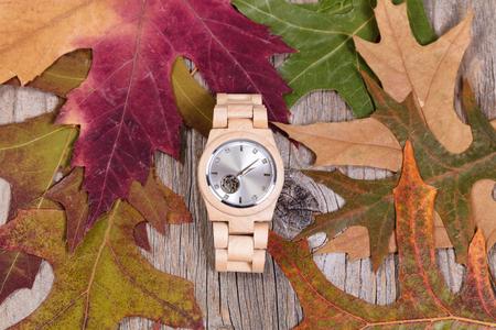 Obenliegende Ansicht des Edelstahl-Uhr mit Herbstlaub und rustikale Holz. Standard-Bild - 64245152