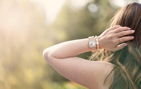 mujeres de espalda: Las mujeres jóvenes, de vuelta hacia la cámara, mirando en brillante luz del día mientras se toca la parte posterior de la cabeza. efecto de la luz aplicada. Foto de archivo