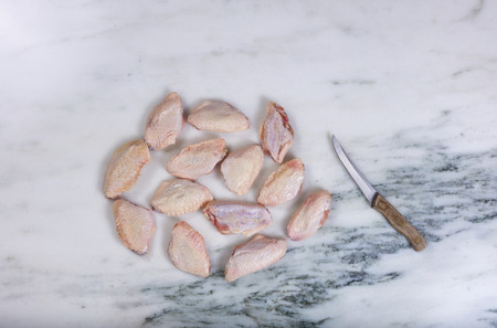 raw chicken: Overhead view of raw chicken wings and kitchen knife of natural marble stone countertop