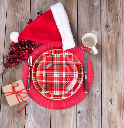 Overhead view of a festive Christmas dinner setting with red berry decorations, Santa cap and present on top of rustic wood Stock Photo