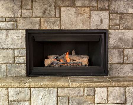 Burning natural gas fireplace surround by stone 版權商用圖片 - 64479994
