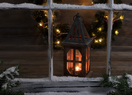 holiday tradition: View of a glowing lantern and Christmas wreath through a snow covered window with fir branches. Stock Photo