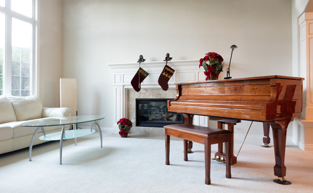 christmas objects: Grand piano surrounded by Christmas objects during with bright daylight coming through the living room window.