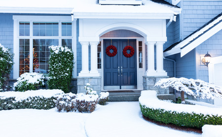 Walkway to a fresh blanket of snow on residential home during the winter holidays.