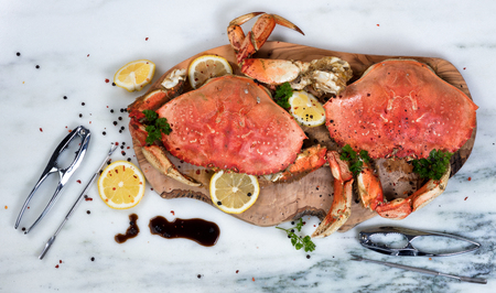 Overhead view of cooked crab on wooden server with utensils and spices  Stock Photo