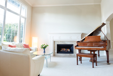 Bright day light coming into living room with burning fireplace, grand piano and white leather sofa.  Banque d'images