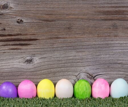 wood grass: Colorful Easter egg decorations on grass with rustic wood in background.