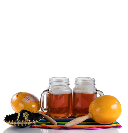 Cinco de Mayo concept with freshly poured beer, maracas, sombrero and placemat serapes on glass table isolated on white.