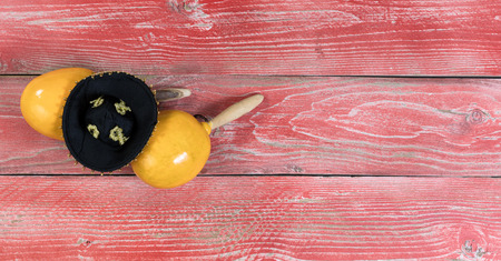 black boards: Flat view of yellow maracas and black sombrero on rustic red wooden boards for Cinco de Mayo concept.