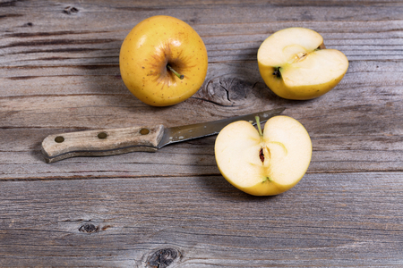 paring knife: Selective focus on sliced golden apple with paring knife and whole apple in background on rustic wooden boards Stock Photo