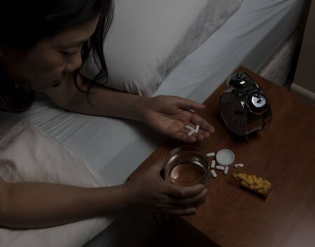 oxytocin: Woman picking up pain killer pills on night stand. Depression and addiction concept. Select focus on hand and pills.