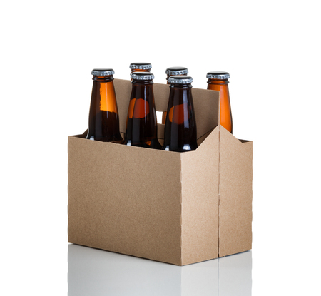 Angled view of a six pack of glass bottled beer in generic brown cardboard carrier isolated on white with reflection 免版税图像