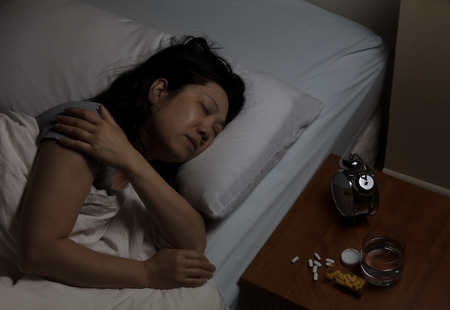 opioid: Mature woman holding shoulder while in pain with pills spilled on night stand.  Addiction to medicine concept.