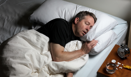 oxytocin: Mature man resting head in pillow while trying to sleep in bed. Insomnia concept with pain medicine on nightstand.
