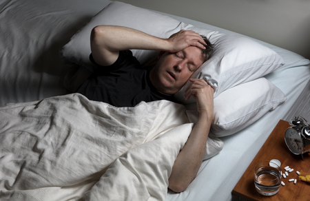 oxytocin: Mature man with hand on forehead while trying to sleep in bed. Insomnia concept with pain medicine on nightstand.