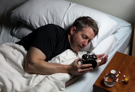 oxytocin: Mature man checking time on alarm clock while preparing to take medicine. Insomnia concept.