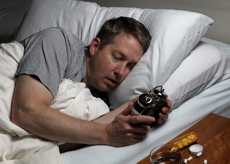 oxytocin: Mature man holding and staring at alarm clock while trying to fall asleep. Insomnia concept.