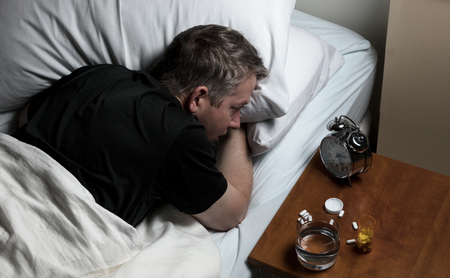 oxytocin: Mature man staring at alarm clock while trying to fall asleep. Insomnia concept.