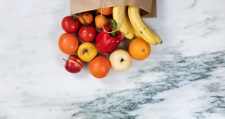 Flat lay view of fruits and vegetables spilling out of a paper bag onto marble stone countertop Stock Photo