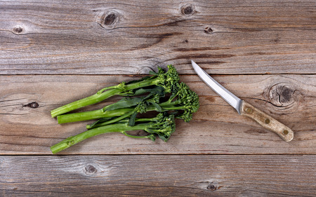 paring: Fresh Chinese broccoli and paring knife on rustic wood in flat lay format Stock Photo
