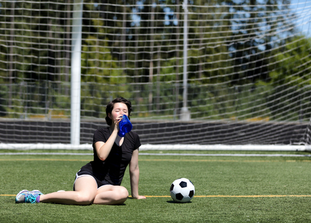 Teen age girl gulping down water during a hot day on the soccer field photo