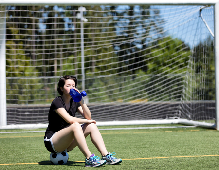 Teen age drinking water from a bottle while on the soccer field during a hot day  photo