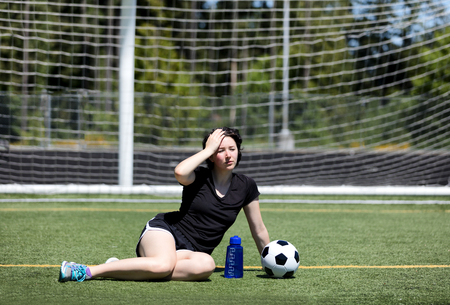 Teen age girl holding her head while resting on the soccer field during a hot day  photo