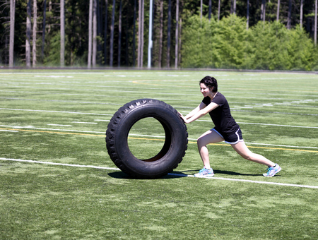 Teen age girl pushing large tire on sports field to build strength Stock Photo