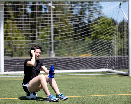Teen age girl resting while on the soccer field during bright hot day photo