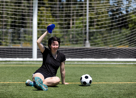 Teen age girl pouring cold water on her head to cool down during a hot day on the soccer field photo