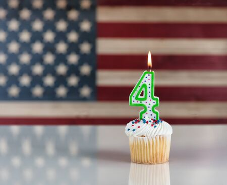 Vanilla cupcake and number four candle with rustic wooden United States Flag in background. July 4th holiday concept Stock Photo