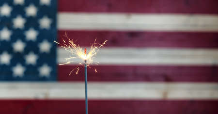 Burning sparkler with rustic wooden United States Flag in background Stock Photo