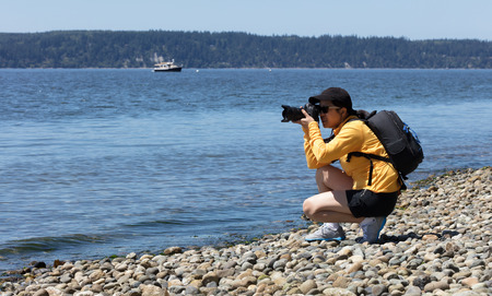 Woman photographer taking photos from shoreline during bright summer day photo